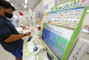 東京都内のコンビニで、キャッシュレス決済が可能なセルフレジを利用する買い物客=9月