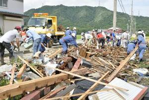 竜巻とみられる突風から一夜明け、後片付けをする住民ら=30日午前、滋賀県米原市