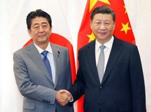 会談で握手する中国の習近平国家主席(右)と安倍首相=12日、ロシア・ウラジオストク(共同)