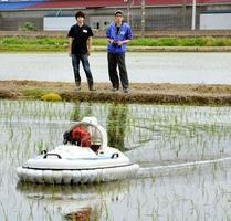除草剤を散布しながら水田の水面を走るラジコン・ホーバークラフト=24日、福井市八重巻町