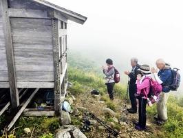 能郷白山の山頂付近にある奥の院で手を合わせる登山者=8月9日