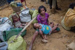 19日、バングラデシュの難民キャンプで妹を抱くロヒンギャの少女(AP=共同)