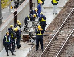 JR千歳線新札幌駅の構内で倒れた信号機の周りに集まる作業員ら=9日午後