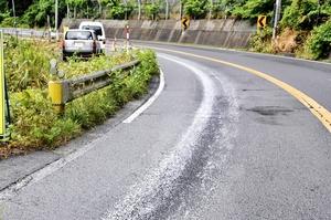 路面の白い付着物。ロウ状になって滑りやすくなっている=7日午前11時35分ごろ、福井県敦賀市の国道8号