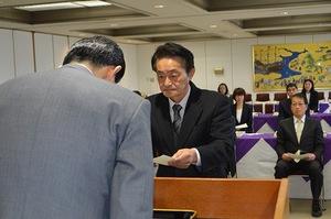 松崎晃治小浜市長(手前)から退職辞令を交付される地村保志さん=31日、福井県の同市役所