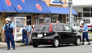 啓蒙小児童の列に突っ込み、横断歩道上で止まった乗用車を調べる捜査員=6月11日午前8時35分ごろ、福井県福井市長本町