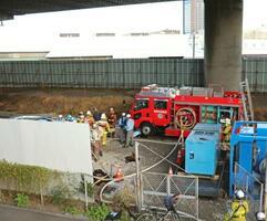 火災があった東名高速道路の高架下に集まった消防署員ら=21日午後、静岡市駿河区