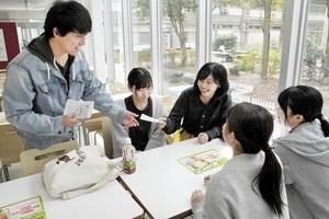 学生たちにチラシを手渡して「幸せ」募集への協力を呼び掛ける八杉有飛さん(左)=4月17日、福井県福井市の福井大学文京キャンパス