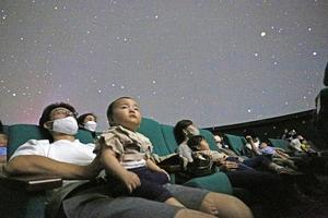 リラックスして星空の映像を楽しむ家族連れ=9月23日、福井県の福井市自然史博物館分館セーレンプラネット