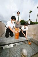 平和公園の「平和の泉」から献水用の水をくむ地元の児童生徒ら=8日午前、長崎市