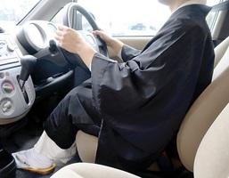 白衣と布袍を着て車の運転席に座る僧侶。仏教界で法事のため僧衣で運転する機会は日常的にあるという=福井県福井市