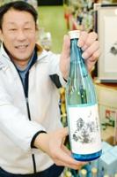 東尋坊限定のオリジナル日本酒を企画、販売している七福屋の西真寿享さん=福井県坂井市の東尋坊商店街