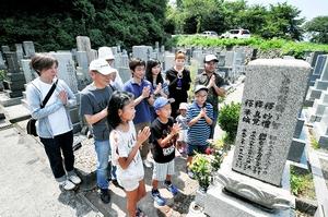 花や線香を供え、先祖の墓参りをする家族連れ=13日、福井市足羽山公園西墓地
