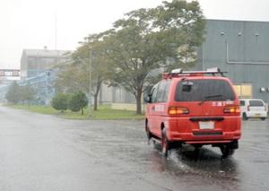 ガス漏れが発生した工場(左奥)の実況見分に向かう嶺北消防の車両=8日午前9時38分、福井県坂井市三国町米納津