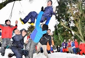 殿上まいりで雪の斜面に放り投げられる男性=5日、福井県鯖江市尾花町