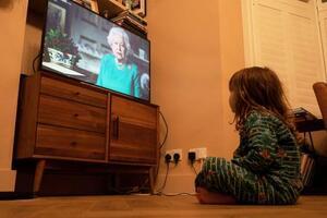 5日、ロンドンでエリザベス英女王の演説動画を見る子ども(ロイター=共同)