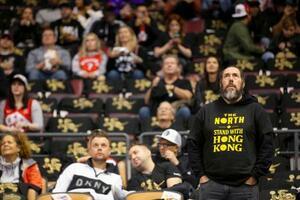 NBA開幕戦で、香港情勢に関しての抗議活動で配られたTシャツを着るファン=22日、トロント(カナダ通信・AP=共同)