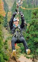 約510メートルを滑り降りながら1年目の決意を発表する内定者=17日、福井県池田町の「ツリーピクニックアドベンチャーいけだ」