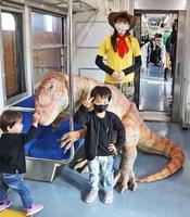 新たに加わったフクイラプトルの恐竜モニュメントやアテンダントと出発前に記念撮影する子どもたち=11月22日、福井県福井市のえちぜん鉄道福井駅