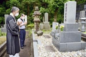 雑草を駆除し、きれいになった墓の前でお参りする高田義紀住職(左)ら=福井県越前市