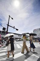 厳しい暑さとなった埼玉県の熊谷駅前を、日傘を差して歩く人たち=8月2日