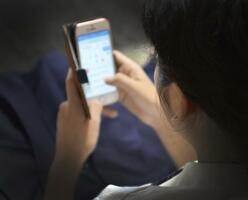 スマートフォンの画面を見る中学生