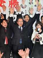 あわら市長選で初当選を確実にし、バンザイする佐々木康男氏(中央)=4日午後9時45分ごろ、福井県あわら市の選挙事務所