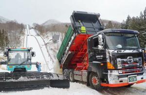 雪をジャンプ台に運搬するトラック=10日、山形市蔵王