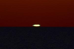 水平線に沈む夕日が緑色に見える「グリーンフラッシュ」現象=18日午後6時55分ごろ、福井市鮎川町(金子俊己さん撮影)