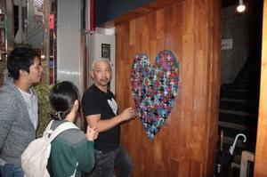 カフェリビング「sumu」の入り口で「ハートアート」を制作する西村さん=2日、福井市のガレリア元町商店街