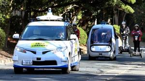 自動運転システムの実証実験で、同時に走行するワゴン車(手前)とゴルフカートの改造車=17日午前、愛知県豊橋市