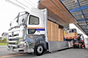 大型トラックに荷を積む運転手ら。長時間労働是正など、業界では働き方改革が急務となっている=福井県福井市寺前町のアイシー物流
