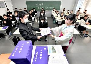 教室で行われた卒業式で担任(右)から証書を受け取る3年生=2月29日、福井県福井市の北陸高校