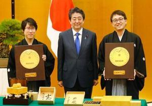 国民栄誉賞を授与され、安倍首相とともに記念撮影する囲碁の井山裕太氏(左)と将棋の羽生善治氏=13日午後、首相官邸