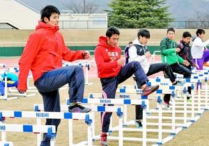 ハードルを使ったトレーニングをする陸上短距離の強化指定選手=福井市の県営陸上競技場