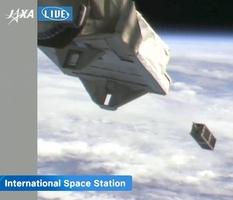 ISSの日本実験棟「きぼう」(手前)から宇宙空間に打ち出される水推進エンジンを搭載した超小型人工衛星=11月20日午後6時25分、JAXAによる動画投稿サイトユーチューブのライブ映像