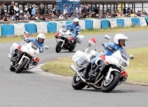 ライダーらが見守る中、サーキットをデモ走行する白バイ隊員=5月26日、福井県福井市西二ツ屋町のタカスサーキット