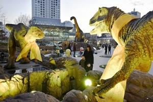 ゴールドリボンで飾られ、ライトアップされた恐竜モニュメント=2月14日夕、福井県福井市のJR福井駅西口