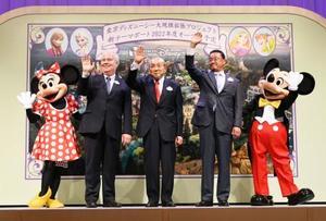 記念写真に納まるオリエンタルランドの加賀見俊夫会長(中央)。右隣は上西京一郎社長=14日午後、千葉県浦安市