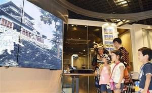 丸岡城と子どもたちが描いたキャラクターが動き出すモニターを見る家族連れら=23日、JR東京駅前の商業施設「KITTE」
