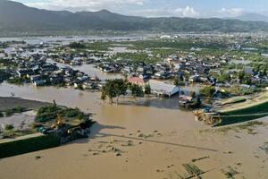 台風19号で千曲川(手前)の堤防が決壊し、住宅地へ濁流が流れ出した現場=13日午後3時53分、長野市穂保(小型無人機から)