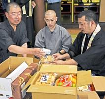 子ども食堂に贈るおやつを段ボールに詰める泰圓澄さん(右)ら=6日、福井県越前市