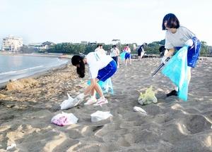 砂浜に散乱したごみを拾い集める三国中生徒たち=8月12日、福井県坂井市の三国サンセットビーチ