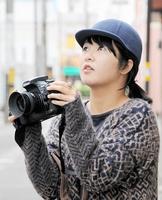 「新たな福井と出合う」をテーマに写真撮影する出地瑠以さん。見上げている先は老舗カフェ=福井市順化1丁目