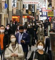 マスク姿で大阪・梅田の繁華街を歩く人たち=27日夜