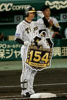 1回、右前打を放ち、長嶋茂雄が樹立した新人最多安打のセ・リーグ記録を更新し、一塁上で記念のボードを手にする阪神・近本=甲子園