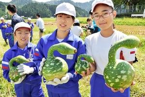 収穫した鹿谷恐竜ひょうたんを見せる児童=21日、福井県勝山市