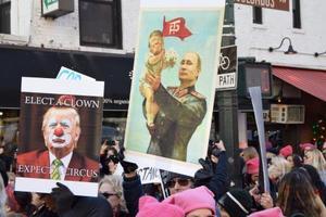 20日、ニューヨークで行われたトランプ大統領に抗議する大規模なデモで掲げられた、ロシアのプーチン大統領にあやされるトランプ氏が描かれたプラカード(中央)(共同)
