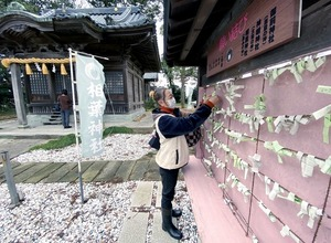 参拝したり、願いごとの紙を結んだりする「嵐」ファン。境内奥に相葉神社がある=12月24日、福井県あわら市宮前の御前神社