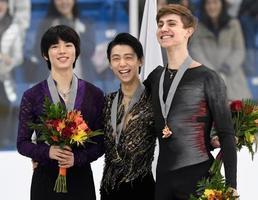 金メダルを獲得し表彰式で笑顔の羽生結弦(中央)。左は2位の車俊煥=オークビル(共同)